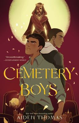 """Cover of """"Cemetery Boys"""" by Aiden Thomas: Two Latino teenagers stand back to back amongst gravestones as a robed skeleton in a flower crown floats behind them, backlit by the moon against a maroon sky"""