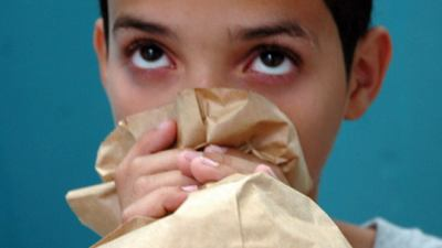 image of girl huffing from brown bag